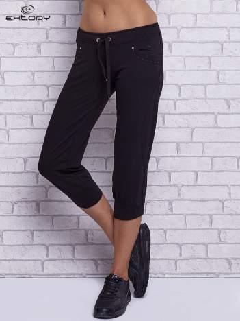 Czarne spodnie capri z dżetami przy kieszeniach
