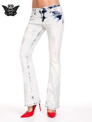 Jasnoniebieskie spodnie jeansowe dzwony z przecieraną i rozjaśnianą nogawką