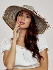 Brązowy kapelusz słomiany z dużym rondem i kwiatem