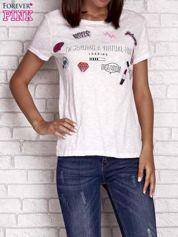 Brzoskwiniowy t-shirt z kolorowymi naszywkami i napisem