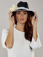 Czarny kapelusz słomiany z dużym rondem i dużym kwiatem