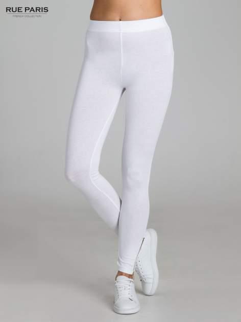 Białe legginsy ze złotym suwakiem na dole