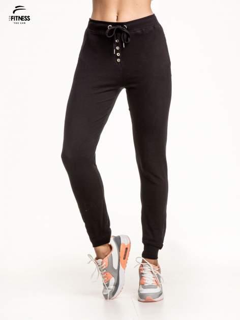 Czarne spodnie dresowe wiązane w pasie z guziczkami
