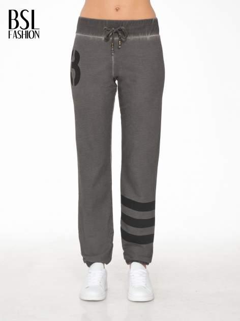 Grafitowe dresowe spodnie damskie z numerkiem i paskami na nogawkach