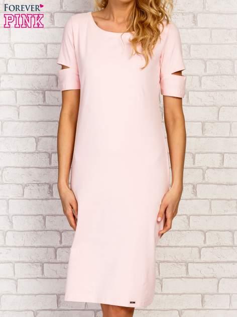 Jasnoróżowa sukienka z rozcięciami na rękawach