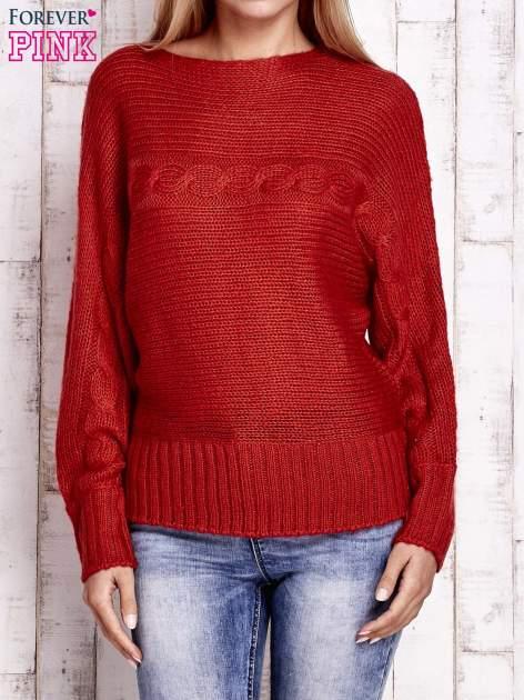 Pomarańczowy sweter z warkoczowym splotem