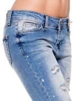 Niebieskie spodnie jeansowe do połowy łydki z licznymi przetarciami