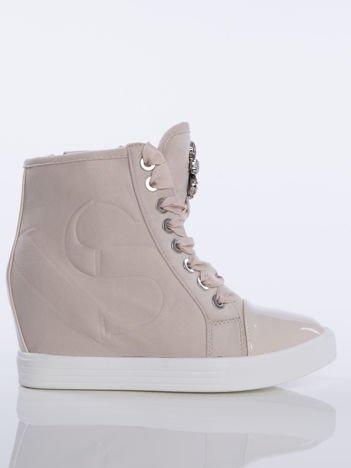 Beżowe zamszowe sneakersy z tłoczoną literką na boku cholewki, sznurowane ozdobną tasiemką z błyszczącymi kamieniami na przodzie