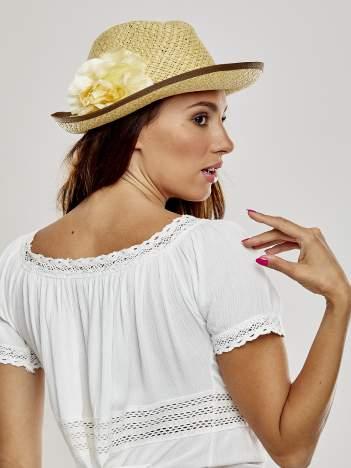 Beżowy kapelusz słomiany z dużym rondem i dużym kwiatem