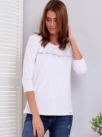 Biała bluzka z delikatnym nadrukiem i dżetami
