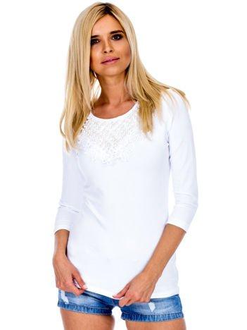 Biała bluzka z ozdobnym dekoltem i perełkami