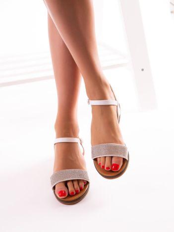 Białe sandały na płaskim obcasie, z mieniącym się paskiem na przodzie