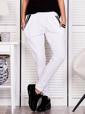 Białe spodnie dresowe ze ściągaczami przy kieszeniach