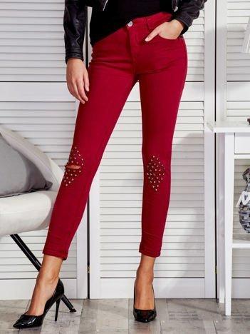 Bordowe spodnie z ćwiekami na kolanach