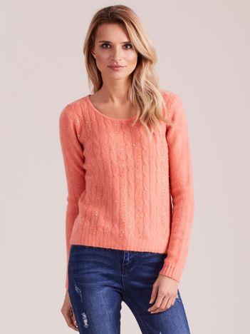 Brzoskwiniowy sweter w warkocze z cekinami