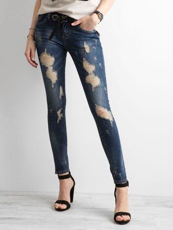 Ciemnoniebieskie jeansy slim fit z przetarciami