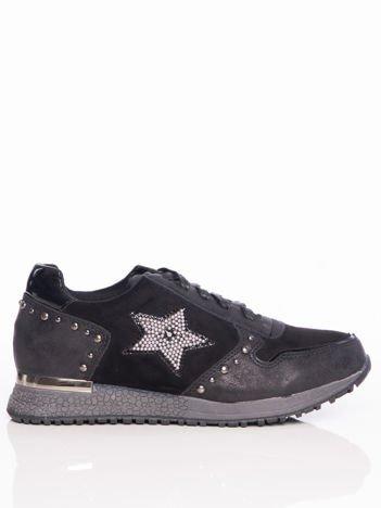 Czarne buty sportowe z ozdobną gwiazdką koralików na boku cholewki, błyszczącymi nitami i lustrzaną wstawką nad piętą