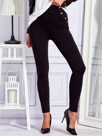 Czarne legginsy ze złotymi guzikami i suwakiem