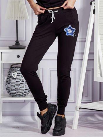 Czarne spodnie dresowe z cekinową gwiazdą