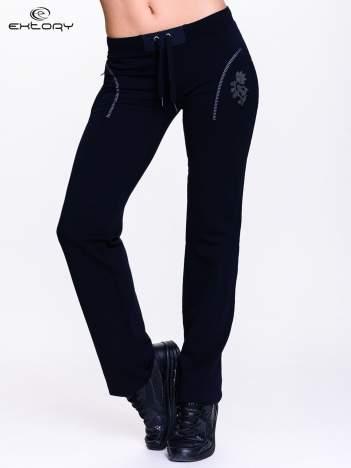 Czarne spodnie dresowe z kwiatem z dżetami i przeszyciem