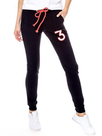 Czarne spodnie dresowe z troczkami i błyszczącą cyfrą