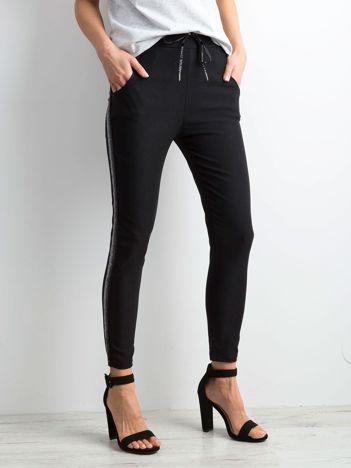 Czarne spodnie z błyszczącym lampasem