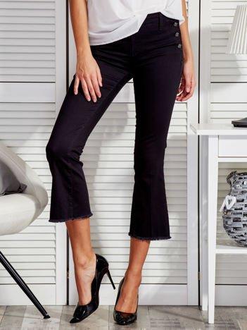 Czarne spodnie z guzikami i wystrzępionymi nogawkami