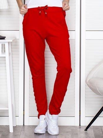 Czerwone spodnie dresowe z błyszczącymi lampasami
