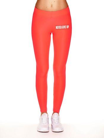 Długie fluokoralowe legginsy na siłownię z napisem NEVER GIVE UP