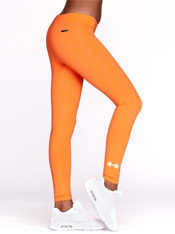 Długie fluopomarańczowe legginsy na siłownię z nadrukiem hantla