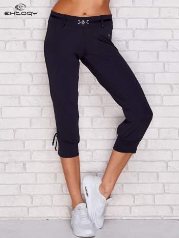 Granatowe spodnie capri z troczkami przy nogawkach