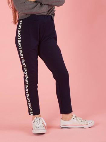 Granatowe spodnie dresowe dziecięce z cekinowym lampasem