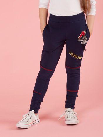 Granatowe spodnie dresowe dziecięce z naszywkami