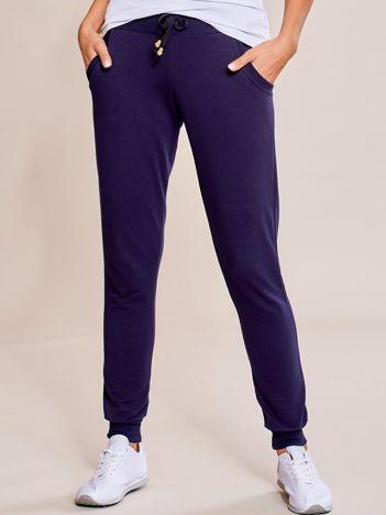 Granatowe spodnie dresowe rurki damskie z kieszeniami