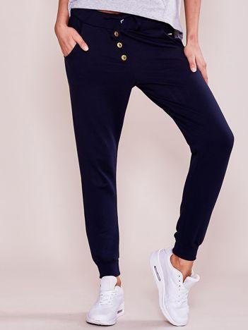 Granatowe spodnie dresowe ze złotymi guzikami
