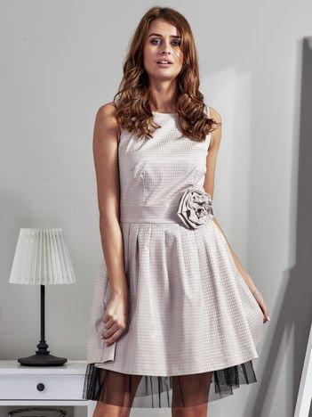 Jasnobeżowa sukienka z ozdobnym kwiatem