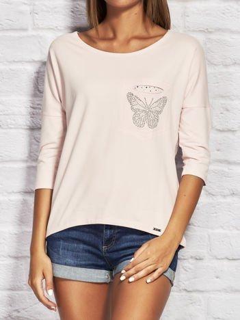Jasnoróżowa bluzka z biżuteryjnym motylem