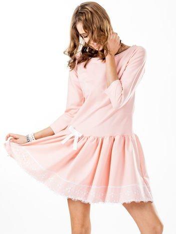 Jasnoróżowa sukienka z kokardką i szeroką falbaną