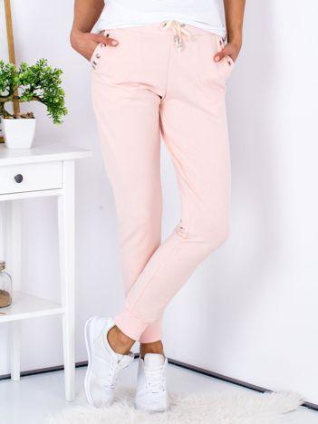 Jasnoróżowe spodnie dresowe z ażurowym wykończeniem kieszeni