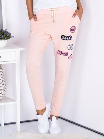 Jasnoróżowe spodnie dresowe z naszywkami