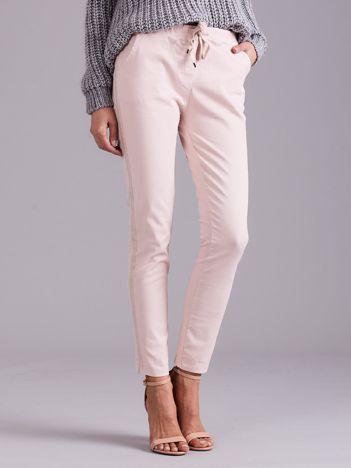 Jasnoróżowe spodnie jeansowe z lampasami