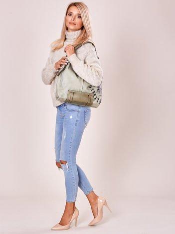 Jasnozielona torba z ćwiekami na pasku i nadrukiem