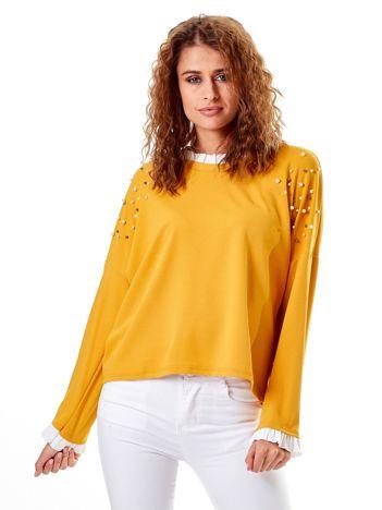 Musztardowa bluzka z perełkami i kontrastowym wykończeniem