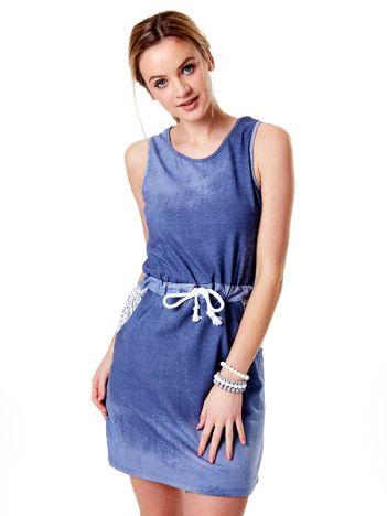 Niebieska sukienka z wiązaniem i koronkowym dekoltem z tyłu