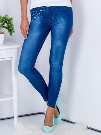 Niebieskie jeansowe spodnie skinny z perełkami na kieszeniach