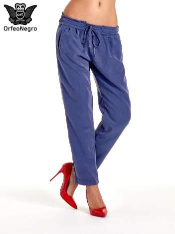Niebieskie lejące spodnie wiązane w pasie