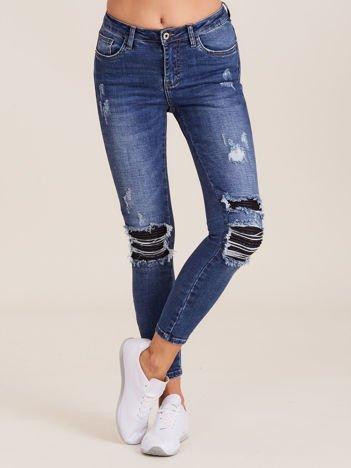 Niebieskie spodnie jeansowe z suwakami i dziurami