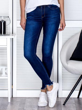 Niebieskie spodnie jeansowe z wystrzępionymi nogawkami