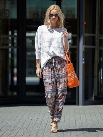 Pomarańczowe spodnie w kolorowe wzory