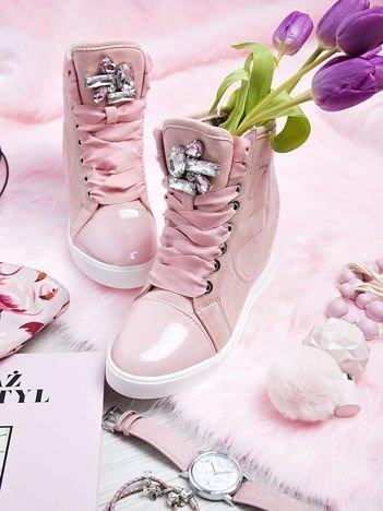 Różowe zamszowe sneakersy z tłoczoną literką na boku cholewki, sznurowane ozdobną tasiemką z błyszczącymi kamieniami na przodzie